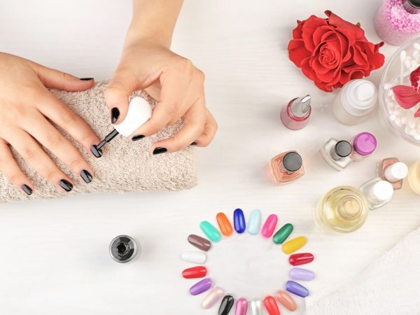 Nail art concept. Woman giving herself manicure on white table