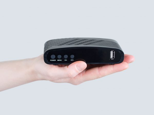 Imagen de una mano sosteniendo decodificador de TV