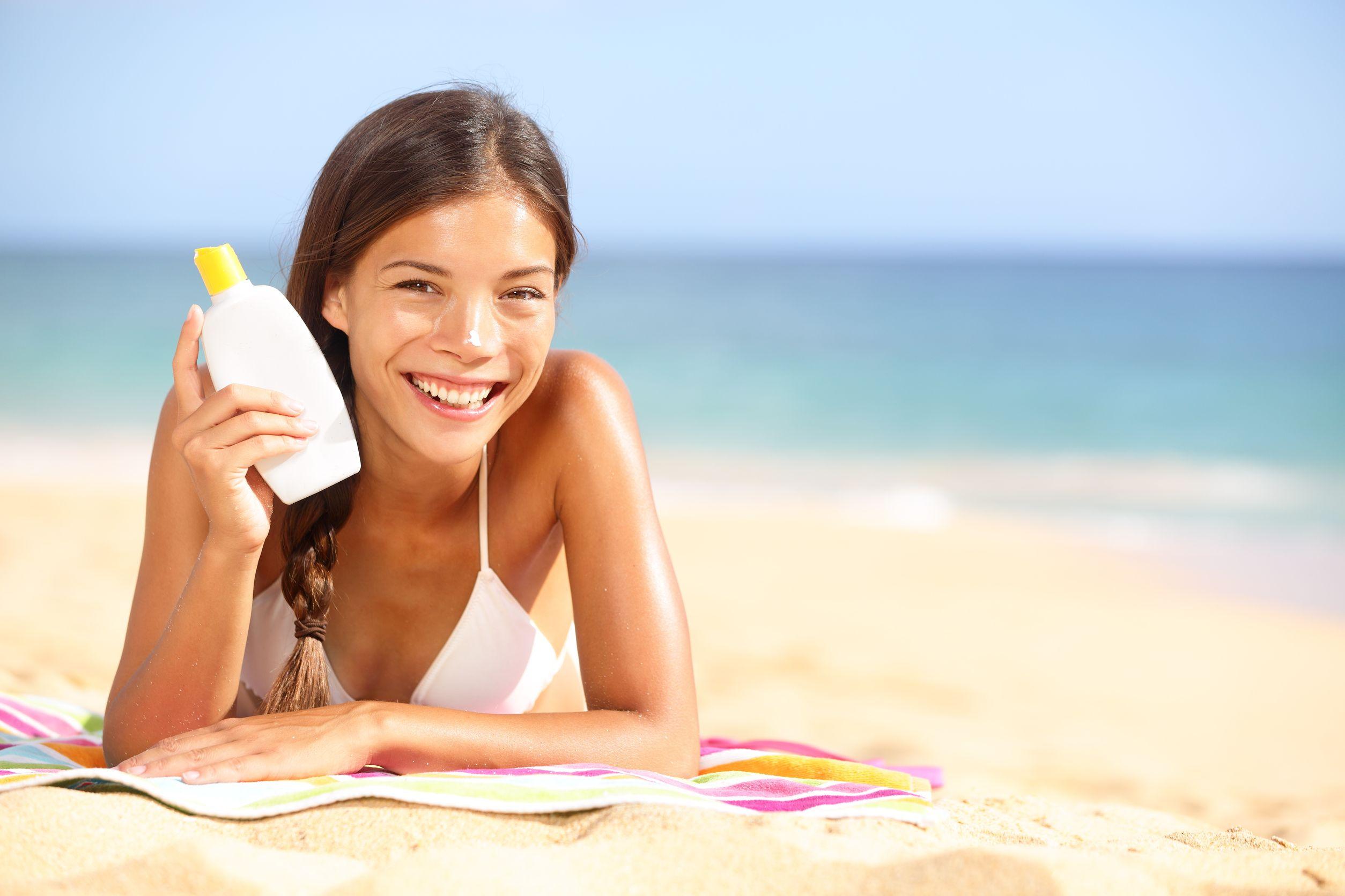 Mujer en la playa sosteniendo protector solar en la mano
