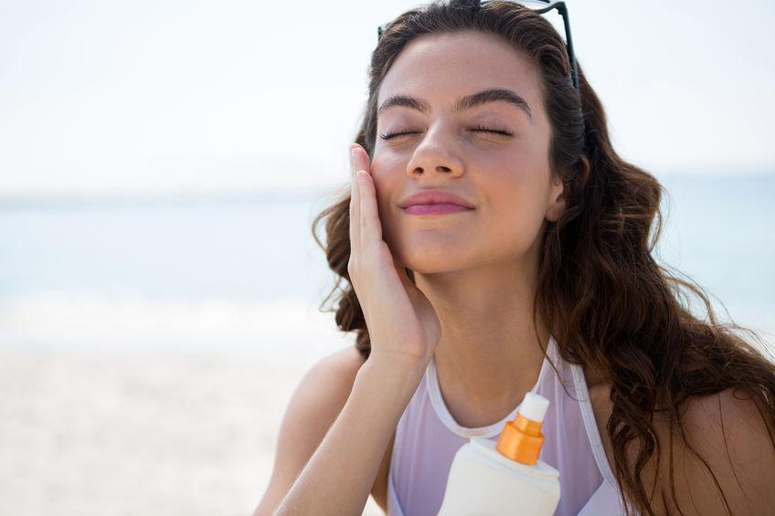 Mujer aplicándose protector solar facial