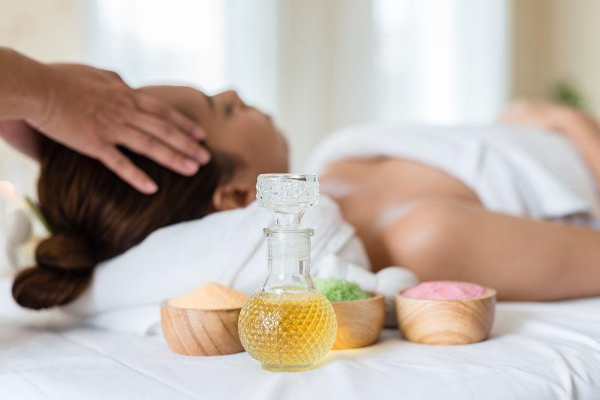 Imagen de un recipiente con aceite, de fondo una mujer recibiendo un masaje