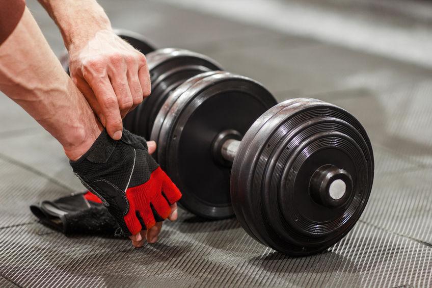 Imagen de una persona levantando pesas utilizando guantes para gimnasio