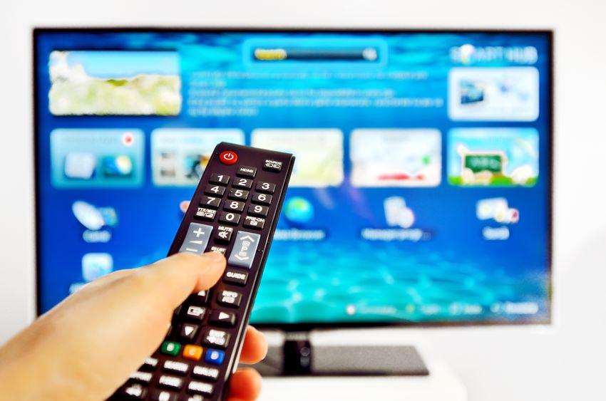 Imagen de una persona con control remoto y un smart TV al fondo