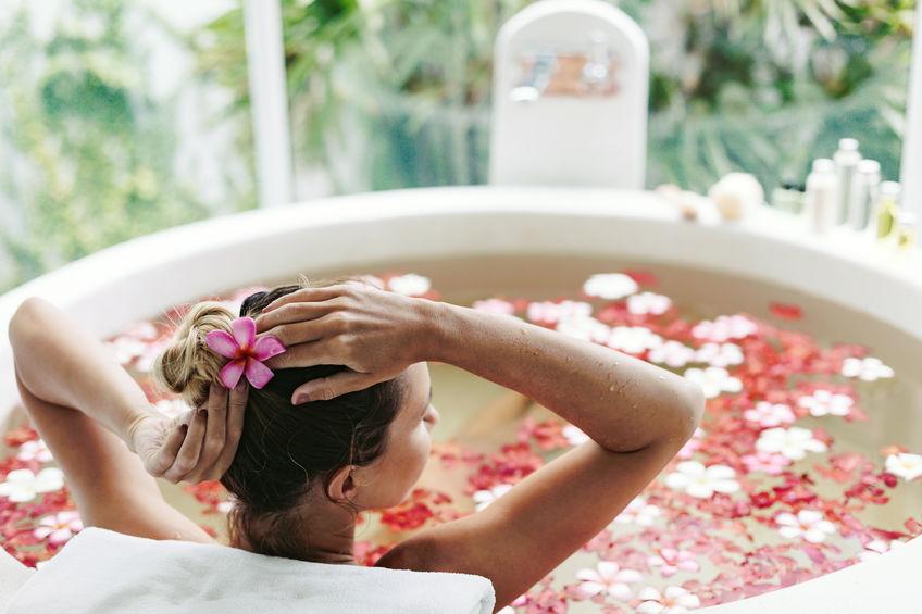 Mujer en bañera con pétalos de rosa