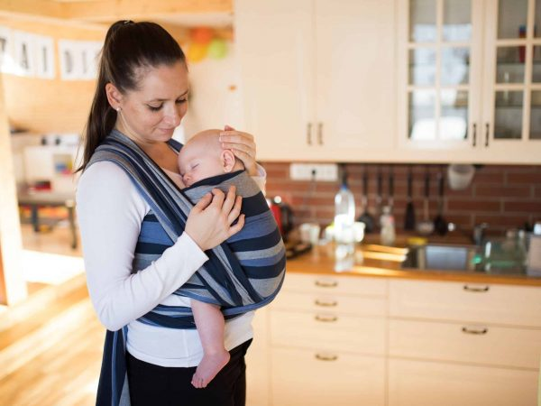 Beautiful young mother in kitchen with her baby son sleeping in sling at home, gently stroking him.