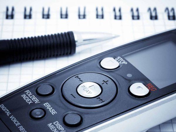 Journalist equipment. Digital  voice recorder, pen and notebook