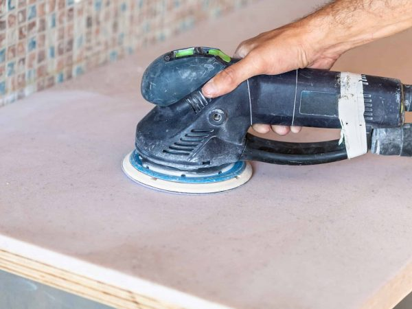 installing new tabletop on kitchen – worker sanding countertop from artificial stone by random orbital sander