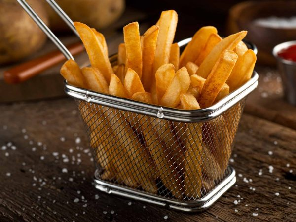 Crispy delicious french fries in a fryer basket.
