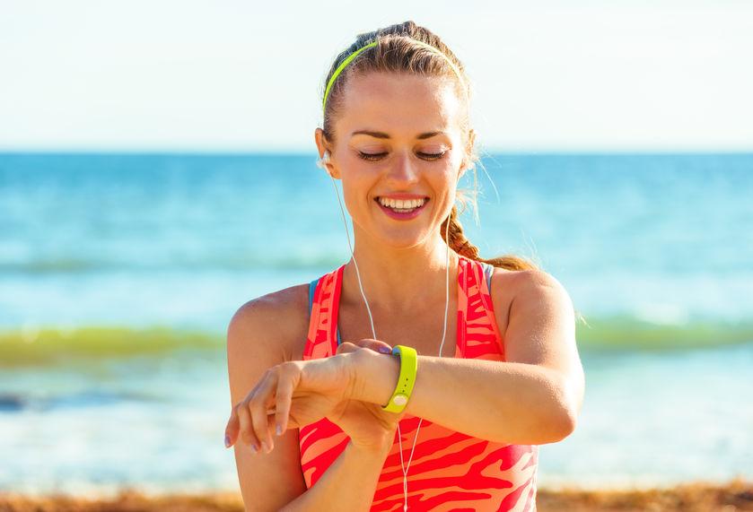 happy healthy woman on seashore looking at activity tracker