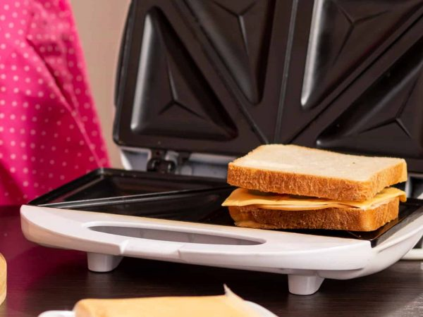 Detail of female hands spreading butter over a bread slice; woman making hot sandwiches in a sandwich maker for breakfast