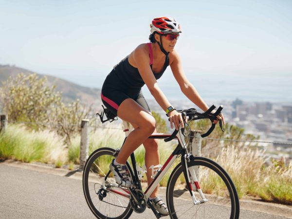 Image of young woman on a bicycle. Caucasian female athlete riding cycle on country road.