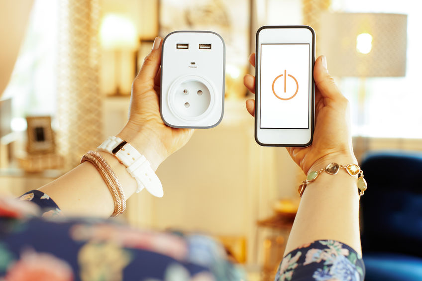 Closeup on smartphone with smart home app and plug in hand