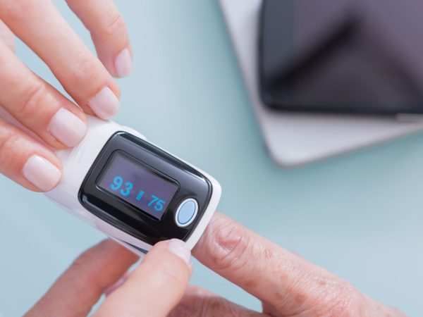 Female doctor and old woman patient using finger pulse oximeter. Unrecognizable. From above, close-up