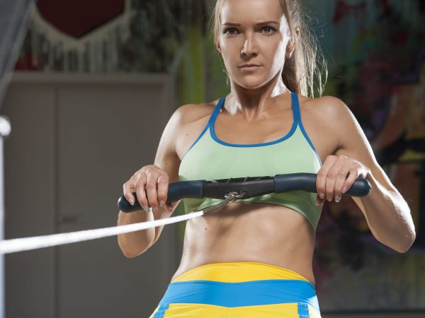 Portrait of confident woman working out on rowing machine. Strong female during intense cardio workout in the gym