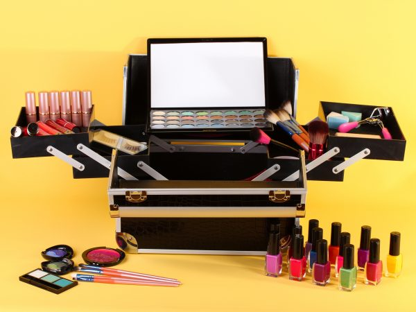 17476984 – open case with cosmetics on yellow background