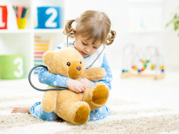 Cute kid girl playing doctor with plush toy at home