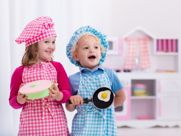 Little girl and boy in chef hat and apron cooking fried eggs in toy kitchen.  Wooden toys for young children. Kids play and cook at home or daycare. Toddler kid playing with stove, pans and dishes.