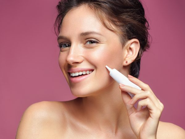 Smiling girl with flawless skin appling treatment cream on pink background. Skin care concept