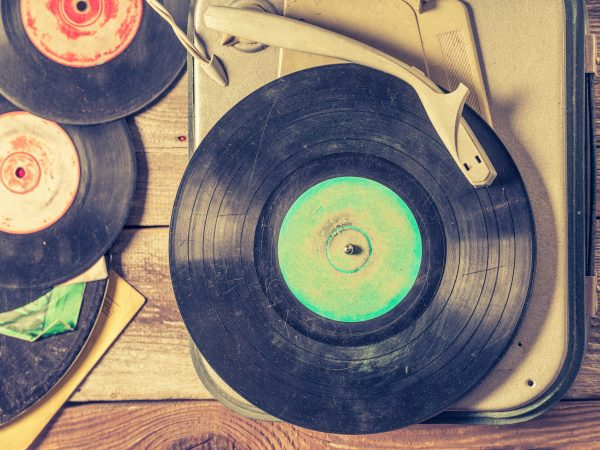 Old gramophone and few vinyl records on wooden table