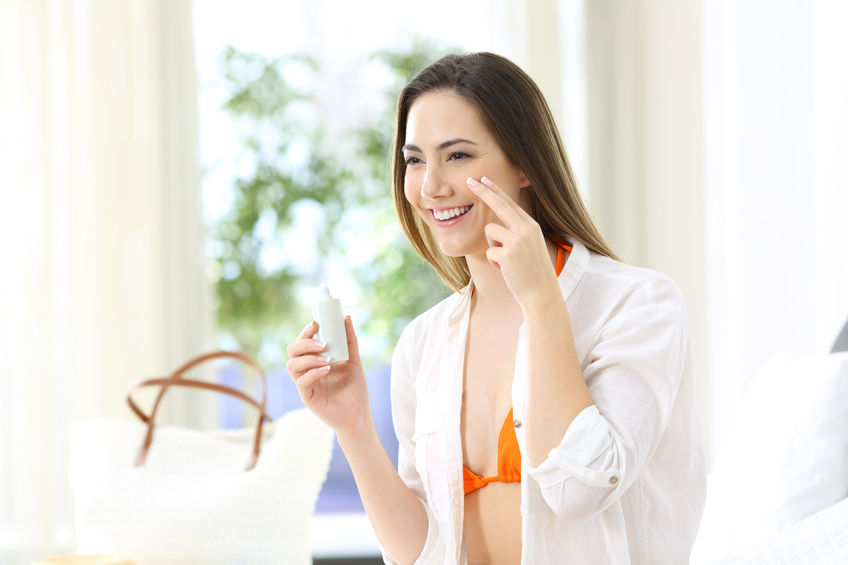Tourist applying sunscreen protection in an hotel room