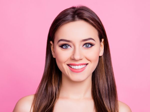 Close up photo of charming wonderful gorgeous pure cute sweet girl with dark brown smooth hair with central parting light coral lipstick eyeliner cat eyes isolated on bright pink background copyspace