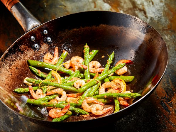 Gourmet prawn and green asparagus seafood appetizer served in an old discolored frying pan on a rusty metal counter in a close up high angle view