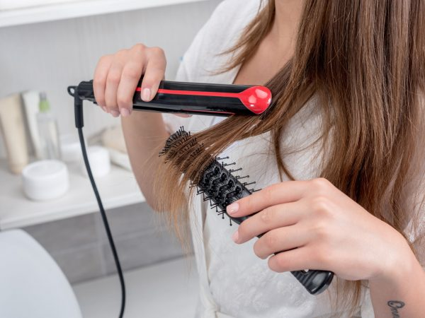 cropped view of young woman in white robe using hair straightener in bathroom