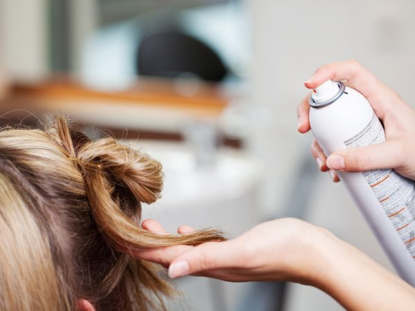 21299606 – closeup of hairdresser's hands using hairspray on client's hair at salon
