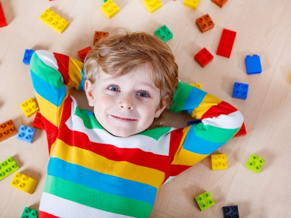 Little blond child playing with lots of colorful plastic blocks indoor. Kid boy wearing colorful shirt and having fun with building and creating.