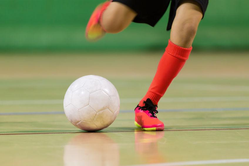 niño juega fútbol sala de fútbol en el pabellón de deportes