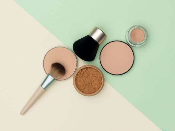 Set of makeup brushes and beige compact powders placed against white and green background