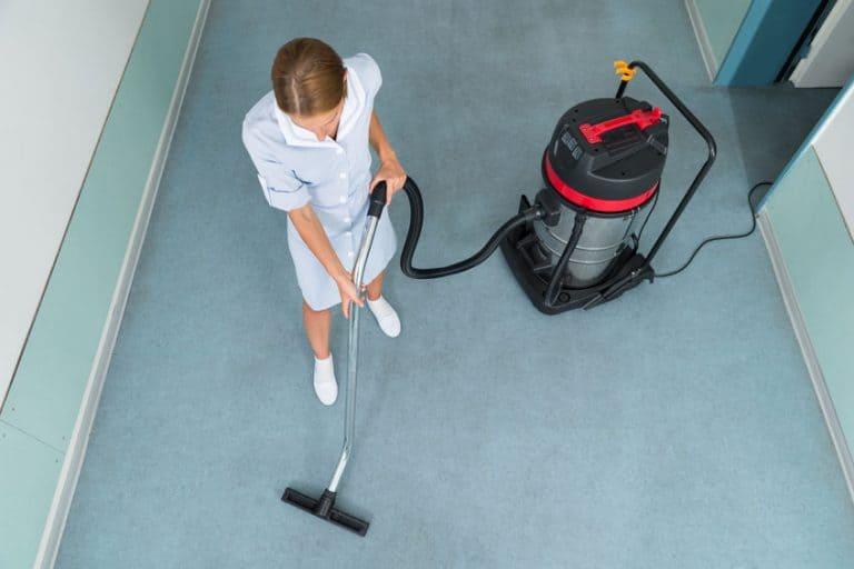 Personal de limpieza aspirando con aspiradora industrial