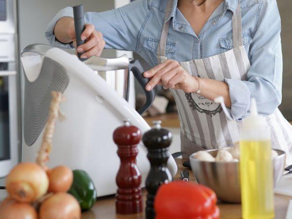 Woman using kitchen robot to prepare dinner