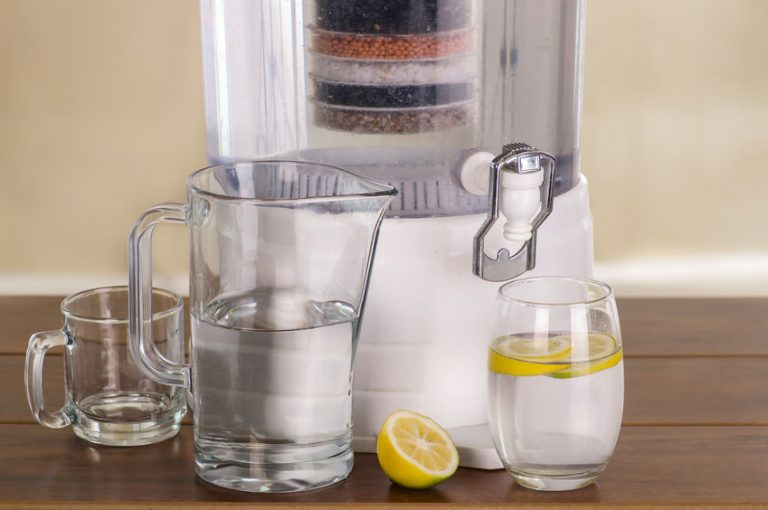 Purificador de agua en mesa con jarra y vasos