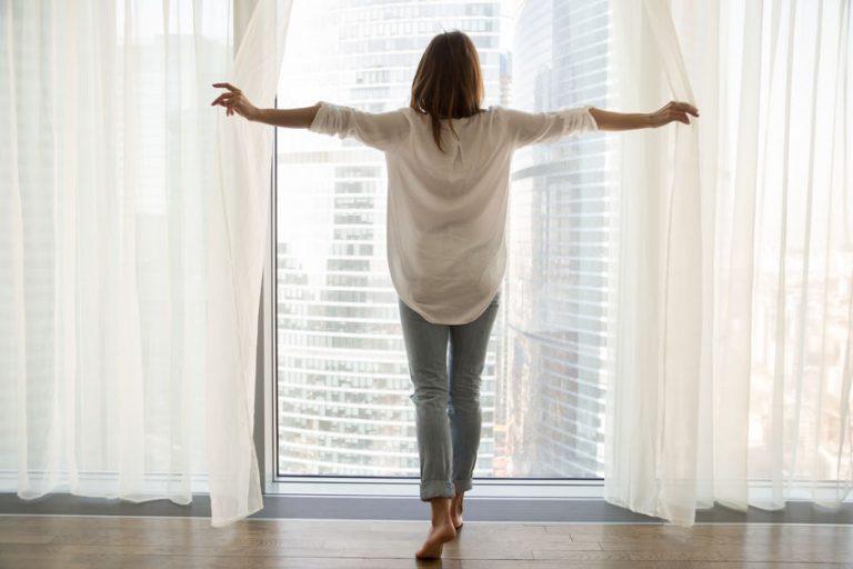 Mujer abriendo cortinas de su casa