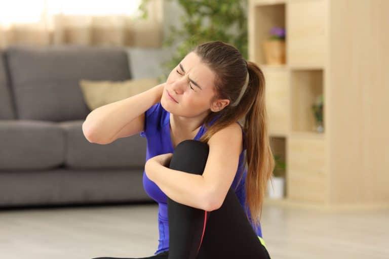 Una chica que le duele el cuello después de hacer deporte