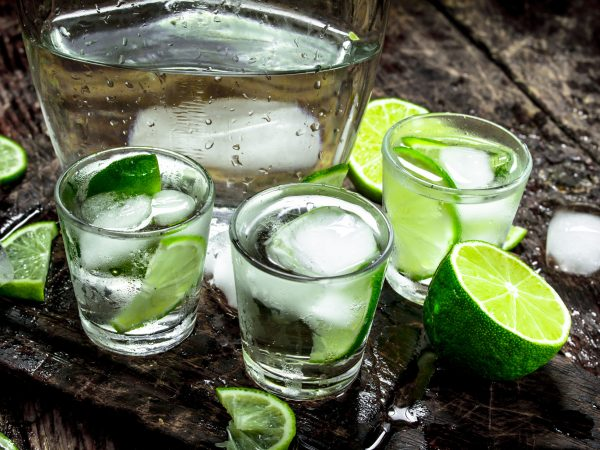 Vodka shots with lime and ice on the board. On a wooden background.