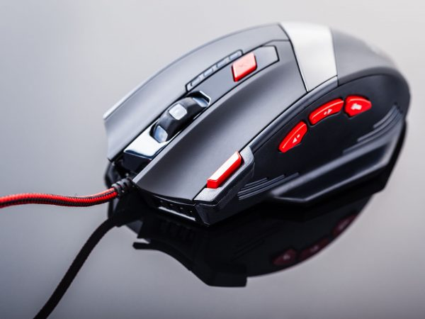 a sleek modern gaming mouse with red buttons over a dark shiny surface