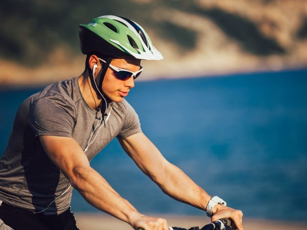 Portrait of mountain biker with helmet and sunglasses listening to music and smiling.