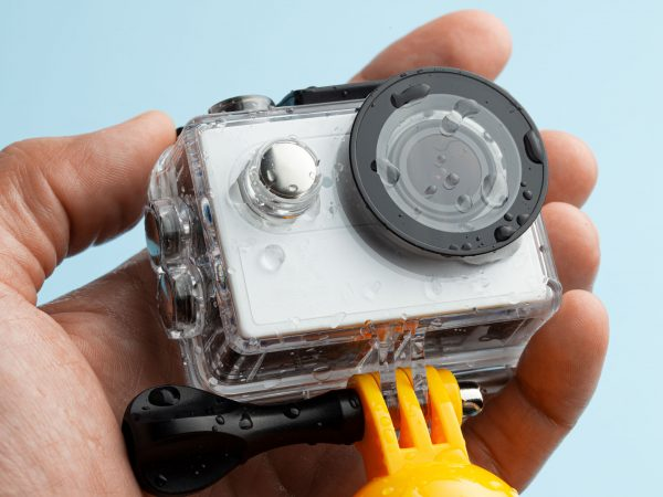 Action camera in a waterproof box and a buoy for diving in drops of water in hand