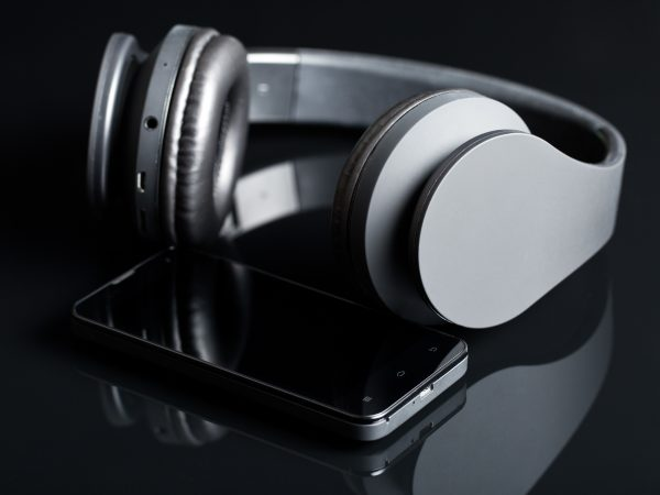 headphones and smartphone on black background