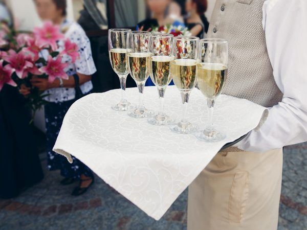 Elegant dressed waiter holding tray with champagne in glasses at wedding reception in luxury restaurant, catering concept