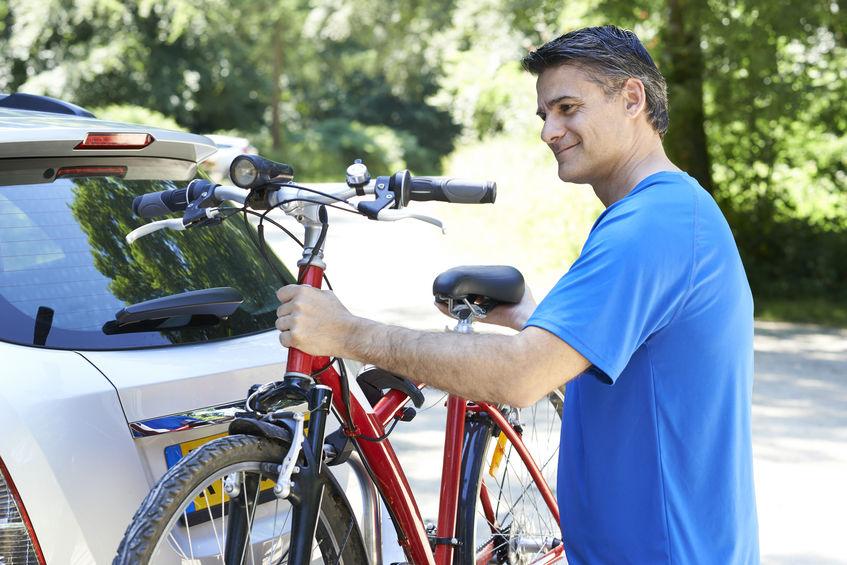 hombre mayor llevando su bicicleta de montaña en auto