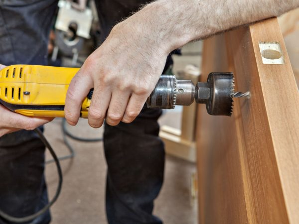 Door installation, hands carpenter holding yellow  power drill with wood hole saw drill bit, drilling through the door to set the lock with a handle, close-up.