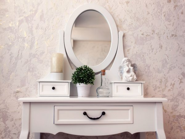 Beautiful wooden dressing table with mirror on white background wallpaper.