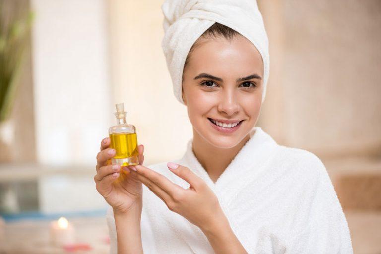 Una mujer sosteniendo un bote de aceite de menta