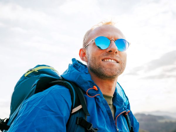 Backpacker man lifestyle portrait enjoying mountain landscape. He wears in blue rain coat poncho and blue sunglasses. Active sports backpacking healthy lifestyle concept.