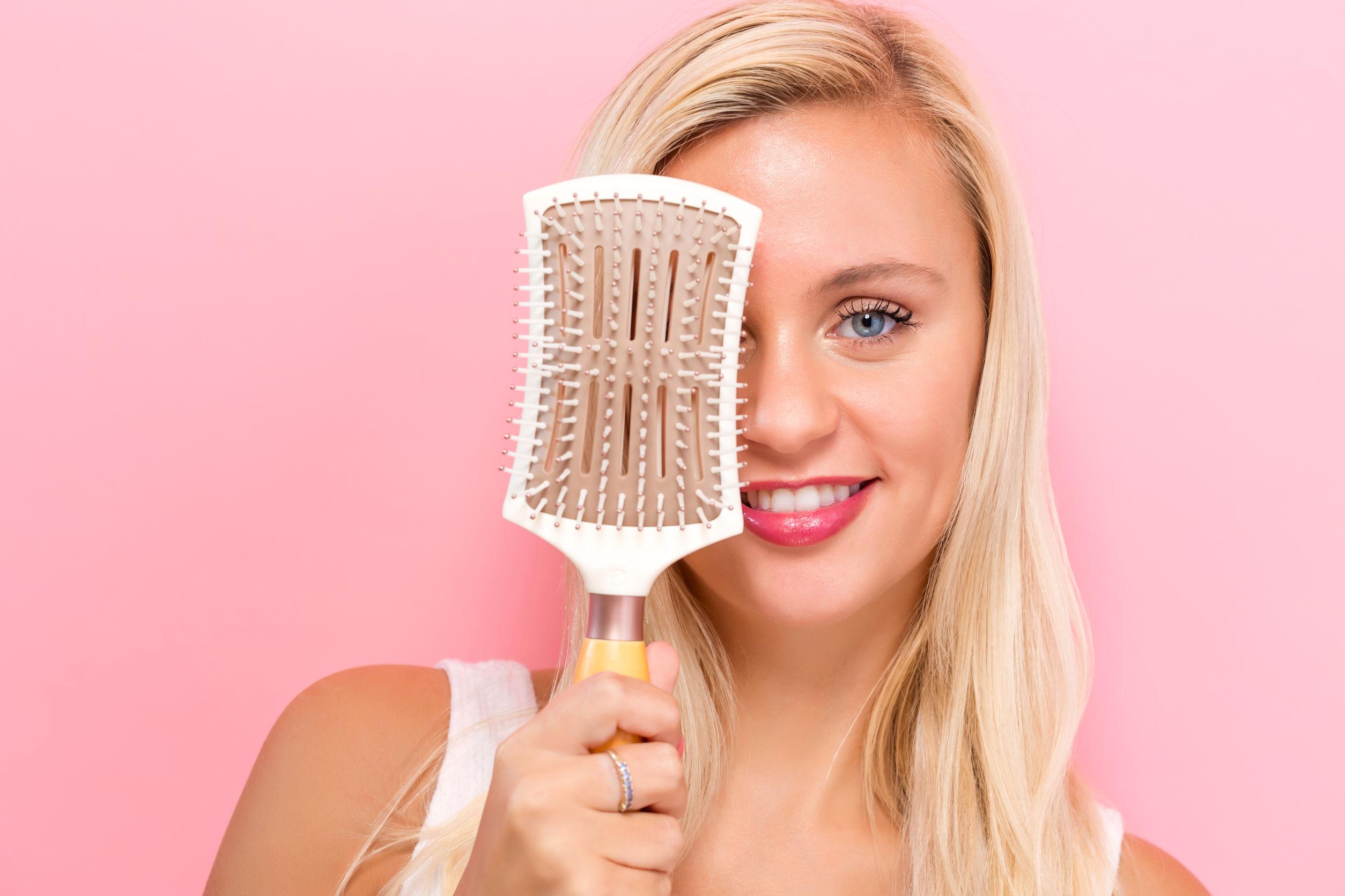 Mujer rubia con cepillo de cabello tapándose la mitad del rostro con fondo blanco