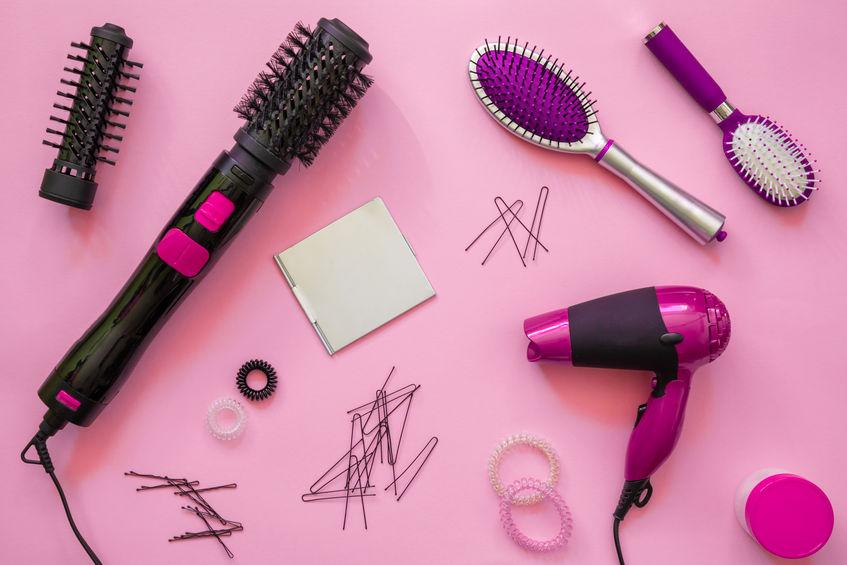 varios secador y cepillo de cabello en fondo rosado
