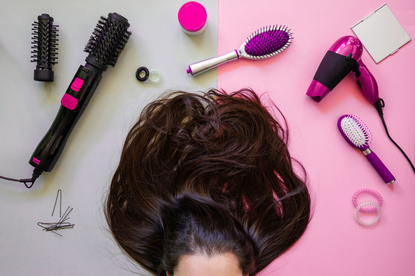 Cabello de mujer junto a utensilios para el cuidado capilar en fondo rosado y gris